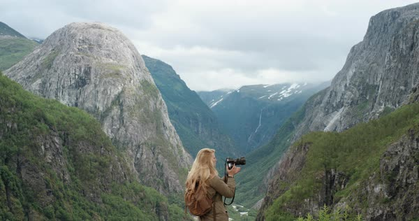 Professional photographer Woman taking photograph of valley with DSLR wearing backpack photographing scenic landscape nature background view enjoying vacation travel adventure Royalty-free stock video