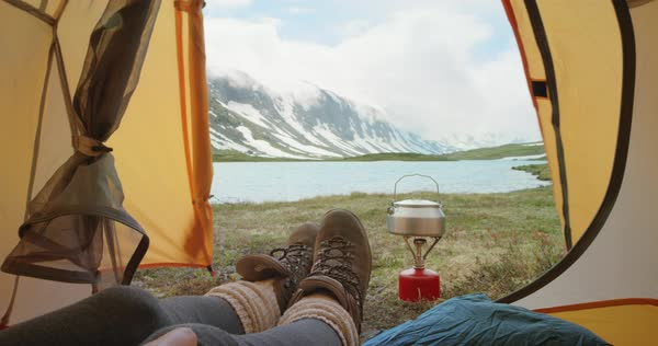 Camping woman lying in tent Close-up of feet wearing hiking boots relaxing on vacation POV Royalty-free stock video