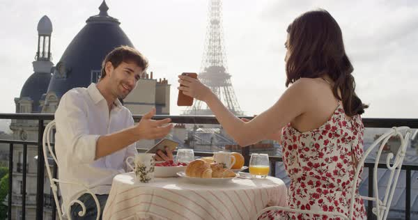 Young couple in Paris hotel enjoying breakfast on terrace woman photographing view of Eiffel Tower at Sunrise with smartphone in the morning Royalty-free stock video