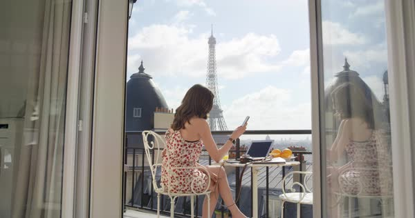 Beautiful young woman holding smartphone digital touchscreen sitting on Hotel Balcony enjoying sunrise view of Paris skyline Eiffel Tower in Background Royalty-free stock video