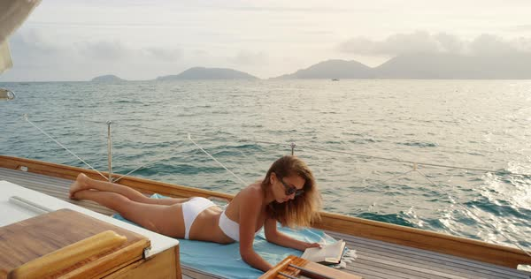 Beautiful woman tanning reading book on sailboat in bikini in ocean on luxury summer lifestyle happy adventure travel vacation Royalty-free stock video