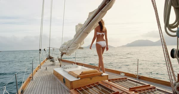 Beautiful woman on sailboat in bikini in ocean on luxury summer lifestyle happy adventure travel vacation Royalty-free stock video