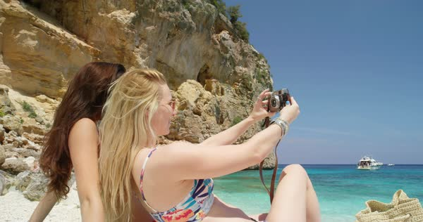 Friends taking selfie photograph with retro styled digital camera woman enjoying tropical beach nature background view on  summer vacation travel adventure Royalty-free stock video