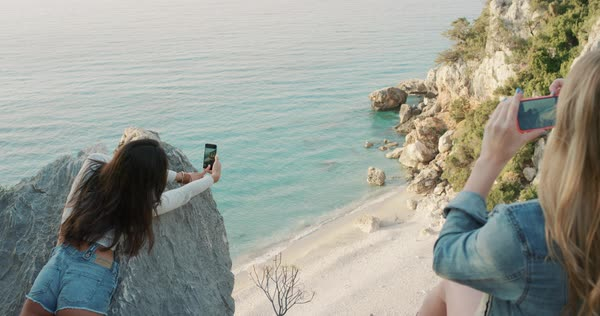 Best friends  taking photograph of each other with smart phone camera leaning over edge of cliff filming beach view at sunrise to share on social media with mobile phone Royalty-free stock video