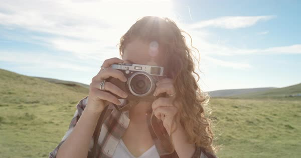 Young woman taking photo with retro styled digital camera at sunset photographing with bright sunny sun flare light creativity Royalty-free stock video