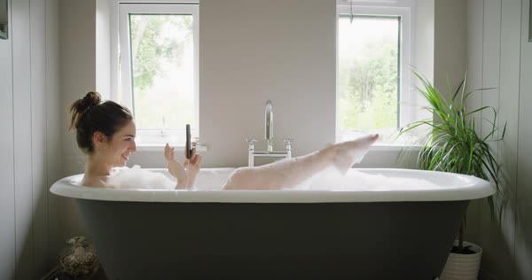 Woman lying in bubble bath taking photos of feet using smartphone sharing creativity on social media relaxing at home Royalty-free stock video