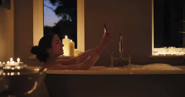 Woman taking selfie enjoying relaxing bubble bath Royalty-free stock video