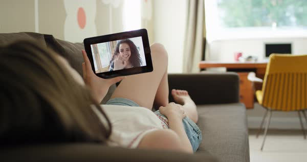 Young woman having video chat holding smartphone webcam lying on sofa at home chatting to girlfriend Royalty-free stock video