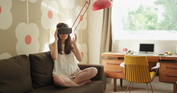 Young woman wearing virtual reality headset sitting on sofa at home watching 360 video Royalty-free stock video