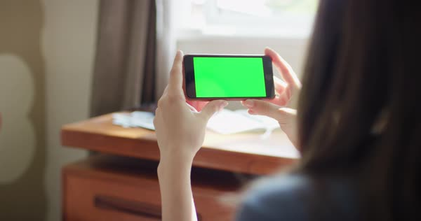 Close-up woman holding smartphone green screen chroma-key green screen sharing social media Royalty-free stock video