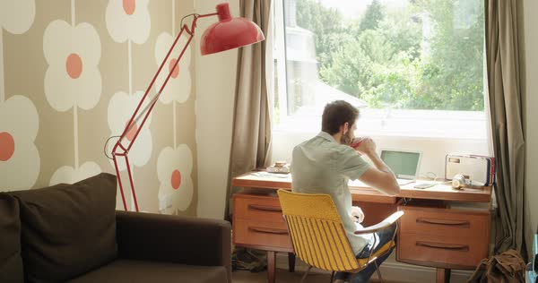Rear view man working at desk using smartphone tablet in retro trendy home office Royalty-free stock video