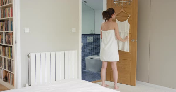 Young woman deciding what to wear taking photo of white dress getting dressed in her elegant apartment wearing white towel  Royalty-free stock video
