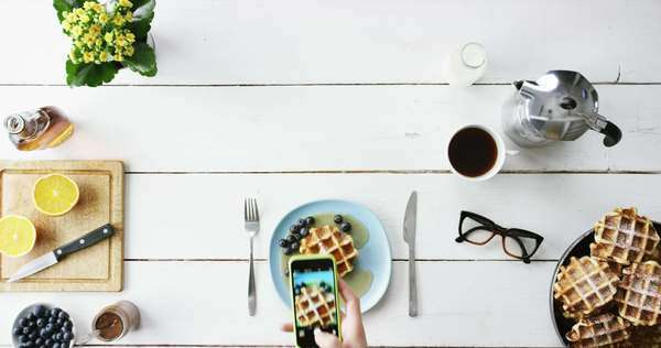 Top view man photographing breakfast using mobile phone Belgian waffles and coffee hands from above Royalty-free stock video