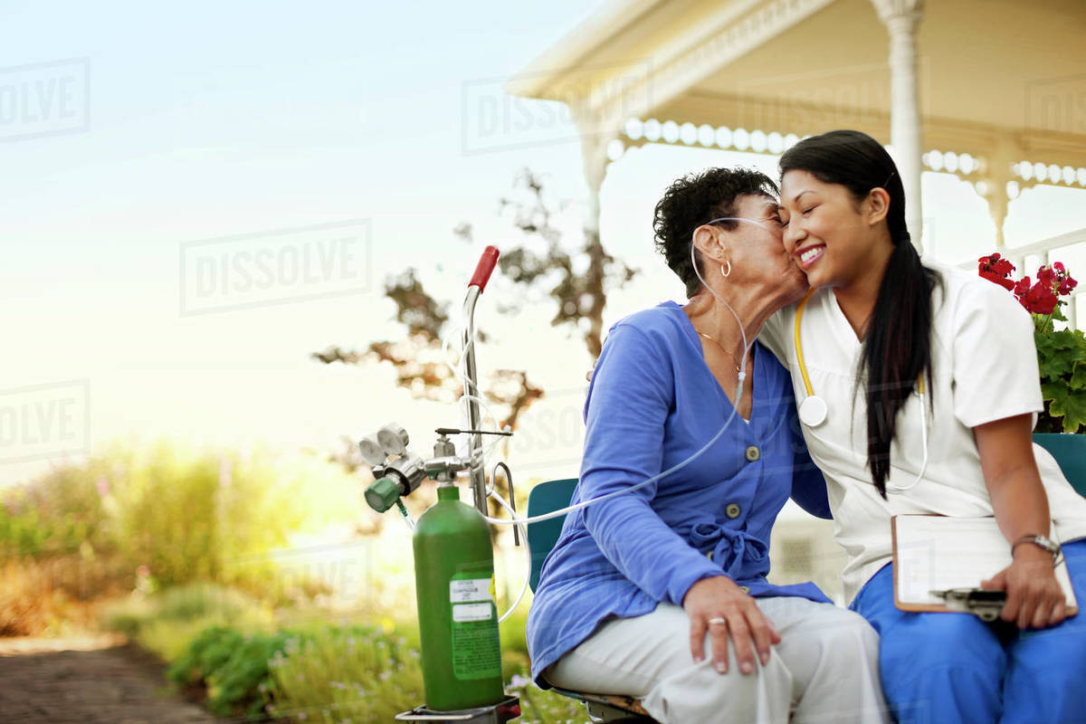 Young female nurse sitting in the garden of an elderly patient with an oxygen tank. Royalty-free stock photo