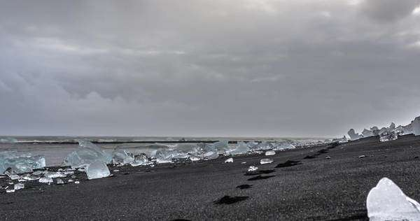 Hyper-lapse icebergs on a black sand beach with foot prints under a cloudy sky. Jokulsarlon Glacier Lagoon, Iceland Royalty-free stock video
