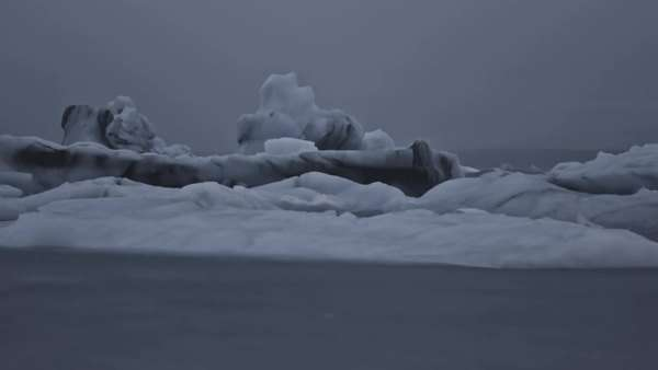 Wide view of Glaciers floating towards the Atlantic ocean at night, jokulsarlon glacier lagoon, Iceland Royalty-free stock video