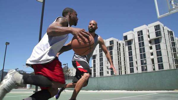 Two basketball players playing one on one outside with scoring Royalty-free stock video