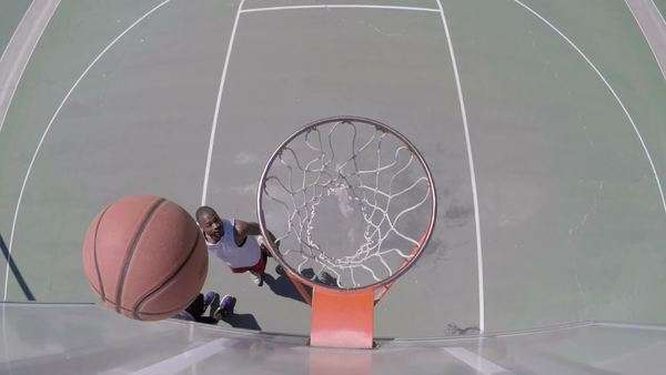 Slow motion overhead angle of two people playing basketball outside Royalty-free stock video