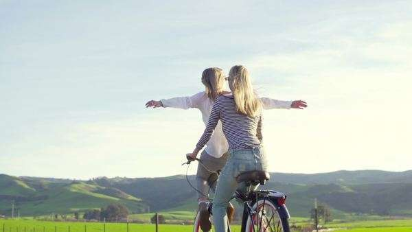 Two best friends walking down country road with bike at sunset Royalty-free stock video