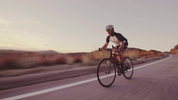 Young fit man cycling on road bike outside at sunset, racing downhill  Royalty-free stock video