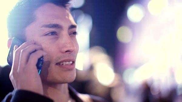 Attractive Asian man talking and laughing on his phone in the city at night Royalty-free stock video
