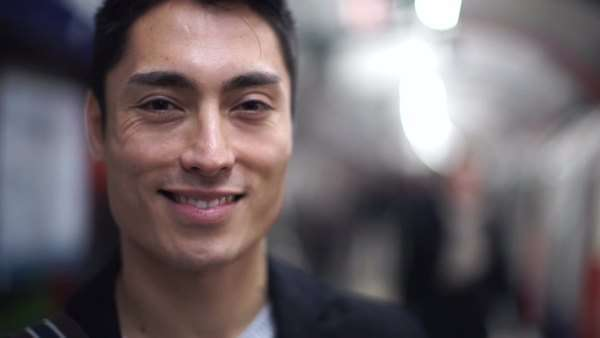 Handsome Asian man smiles to camera in a subway station Royalty-free stock video