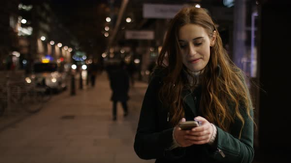 Attractive young woman walking through the city at night on her phone, in slow motion Royalty-free stock video