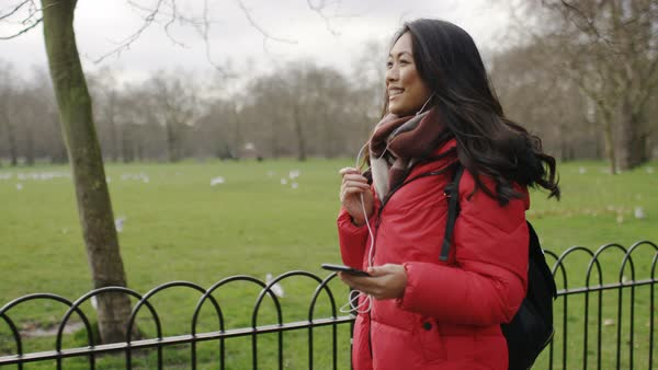 Young woman talking on her phone as she walks in a park Royalty-free stock video