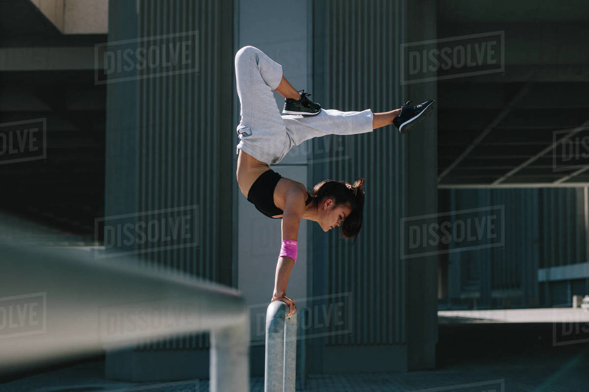 Woman doing a handstand on railing outdoors. Flexible female performing extreme sports in urban city space. Royalty-free stock photo
