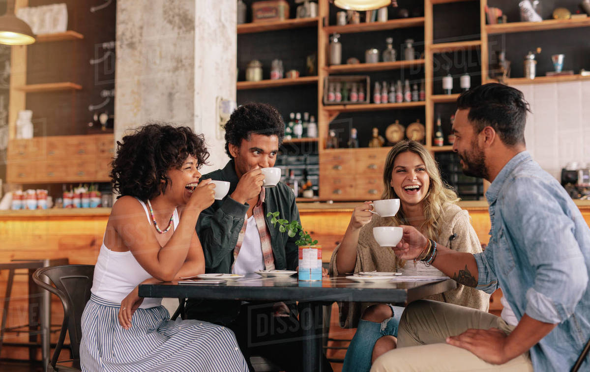 Diverse group of friends enjoying some coffee together in ...