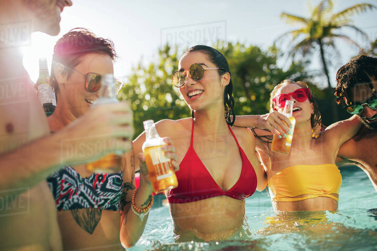 Cheerful group of friends having great time at pool party. Group of men and  women enjoying together in the swimming pool with drinks. stock photo