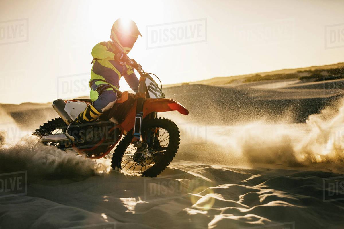 Biker riding dirt bike on the sand dune  Motocross off roading in desert   stock photo