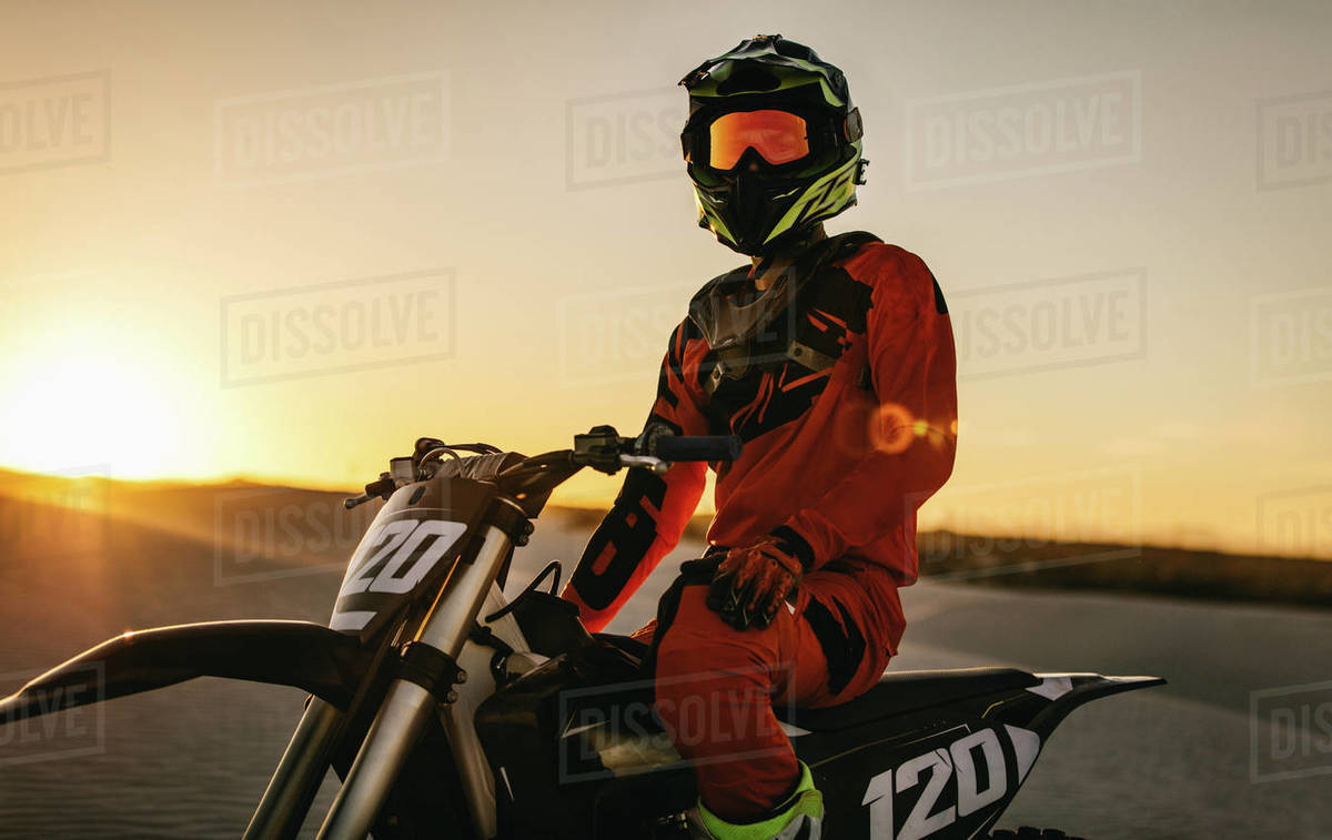 Professional motocross rider sitting on his bike in a desert. Motorcycle rider ready to race on the sand dunes during sunset. Royalty-free stock photo