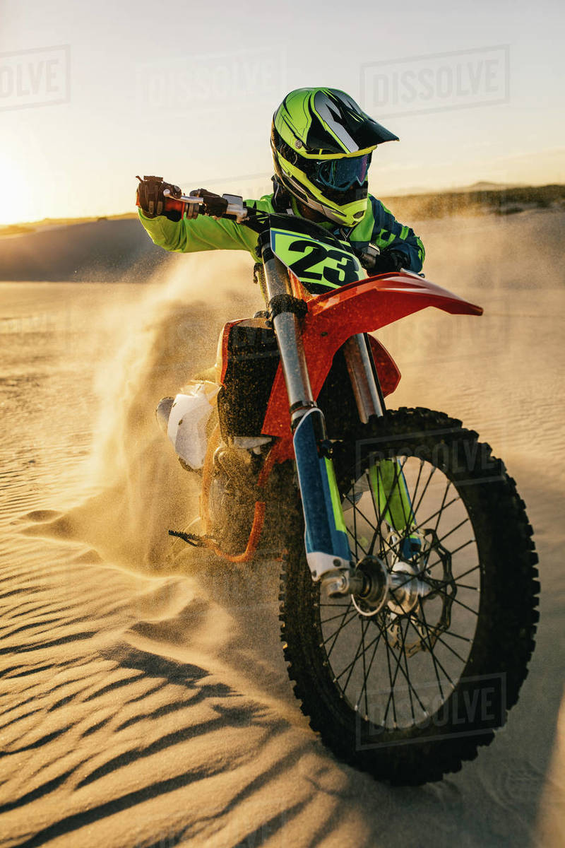 Motocross rider riding his bike on a sand dune. Motorcycle rider in racing gear riding his bike up the sand dune leaving behind sand dust. Royalty-free stock photo
