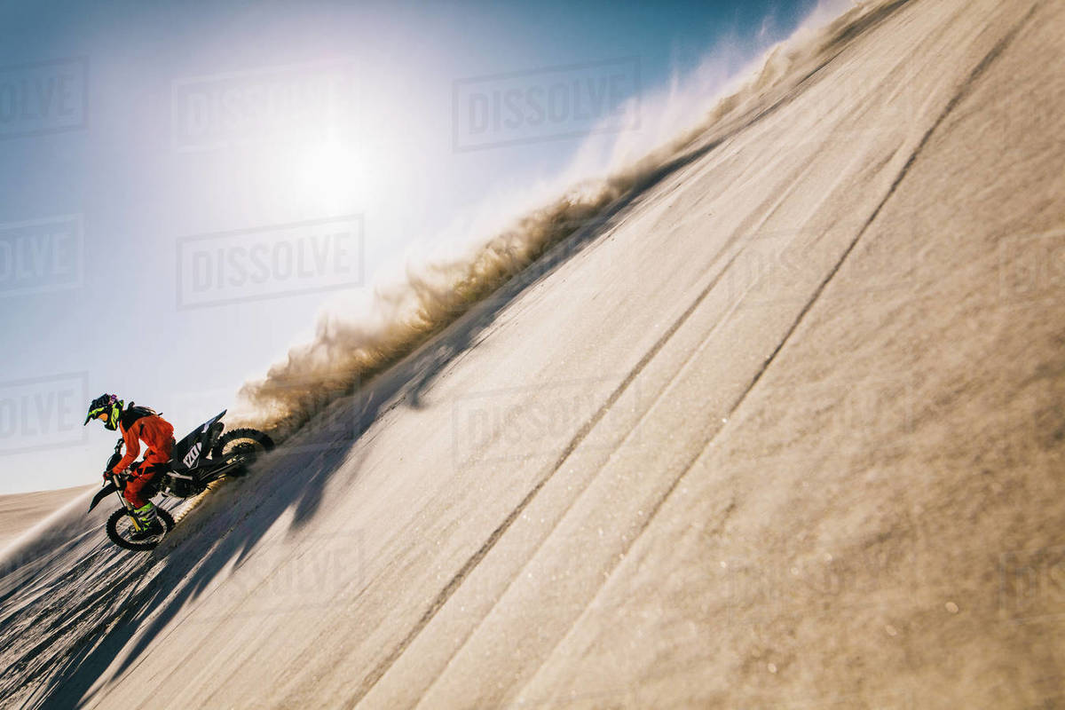 Motocross rider riding on his bike down a sand dune leaving a trail of sand dust. Motorcycle rider driving on the dunes with sun in the background. Royalty-free stock photo