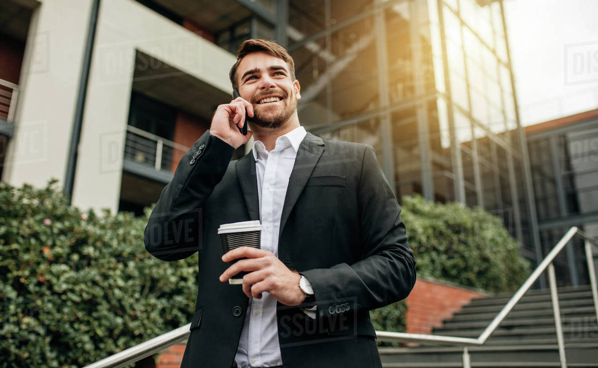 Businessman walking out of office with coffee and talking over cell phone. Businessman in formalwear walking down the steps making a phone call. Royalty-free stock photo