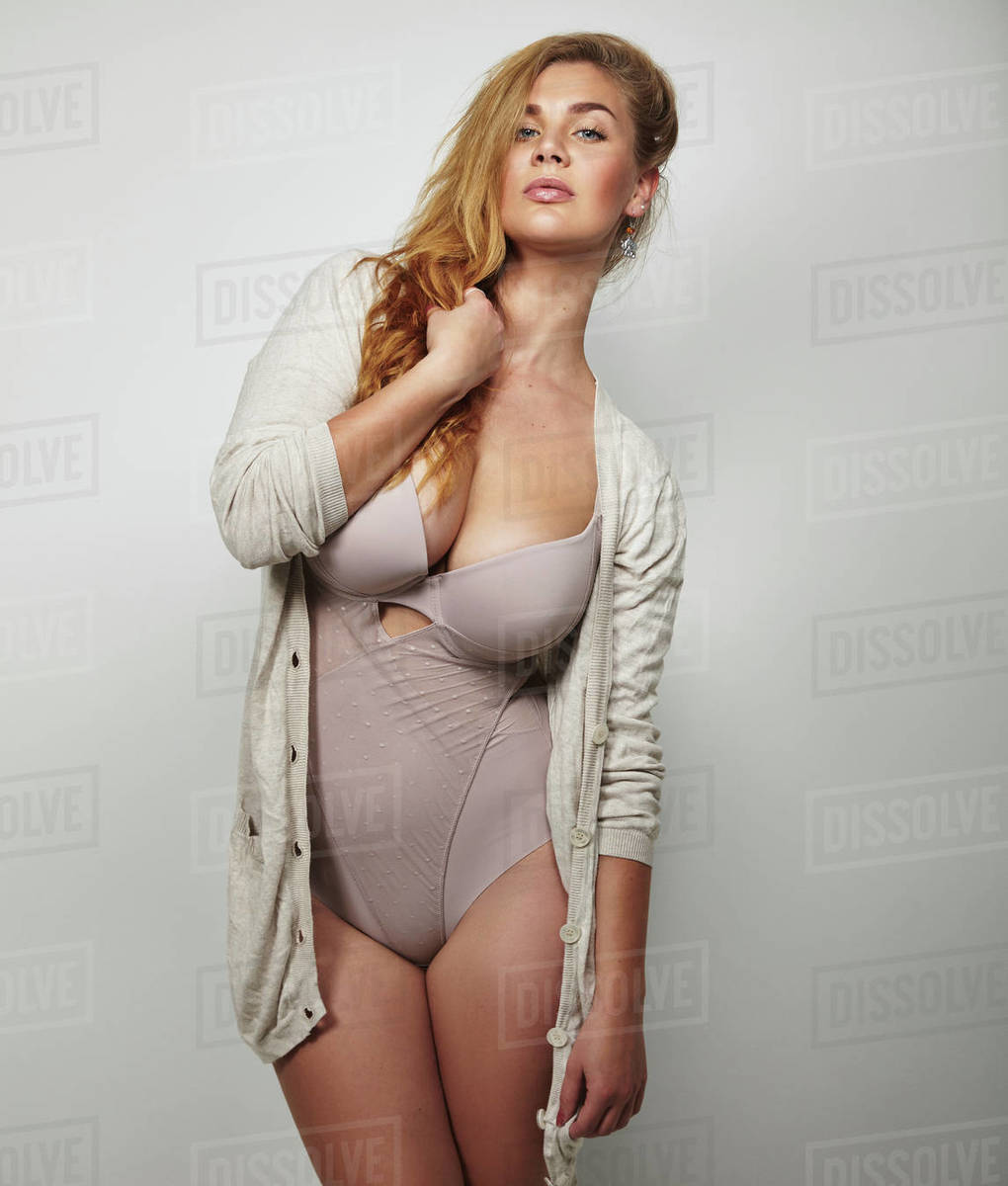 c3e15837026 Overweight woman in underwear posing confidently against grey background. Plus  size model in body stocking looking at camera.
