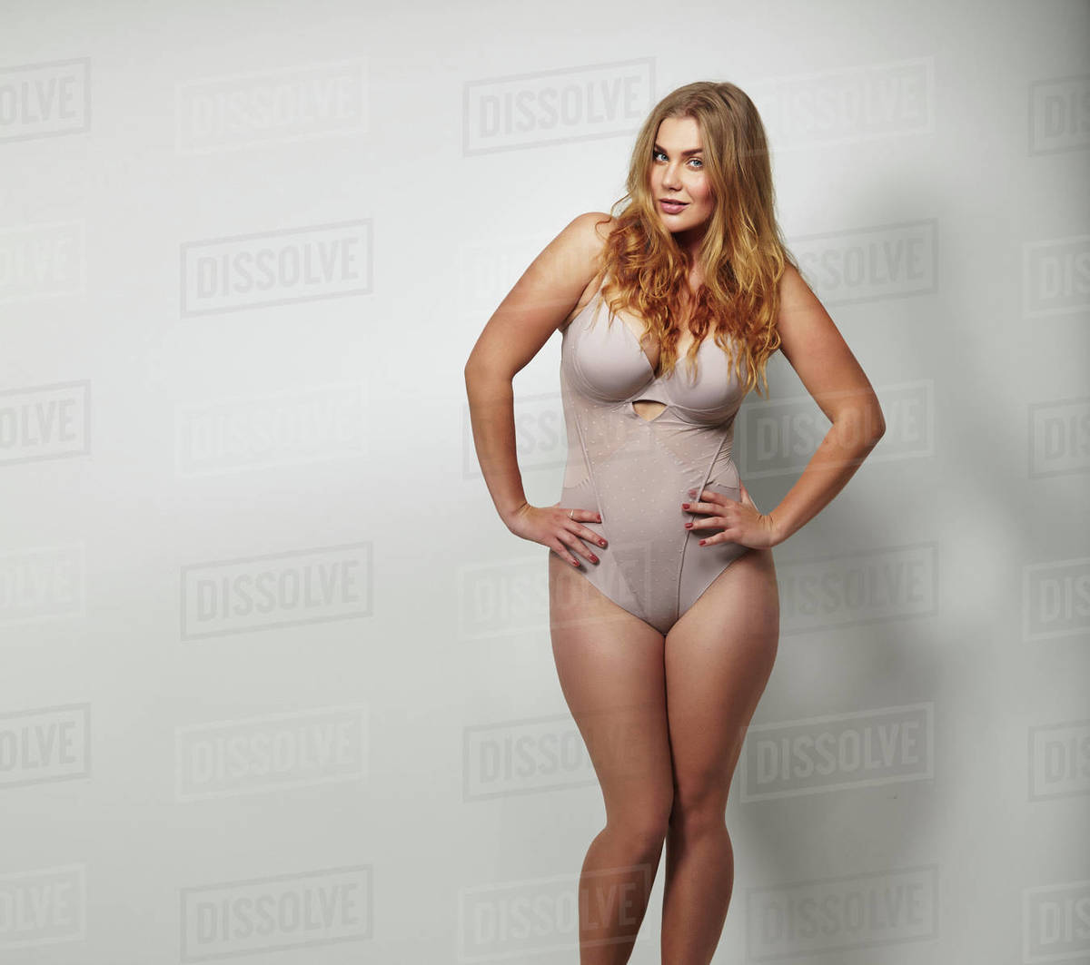 582f448f7cb Chubby young woman in body stockings standing on grey background with her  hands on hips looking at camera. Caucasian plus size female model in  lingerie with ...
