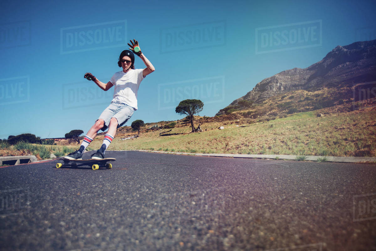 Young man longboarding on a road. Young guy wearing protective gear skating on rural road. Royalty-free stock photo