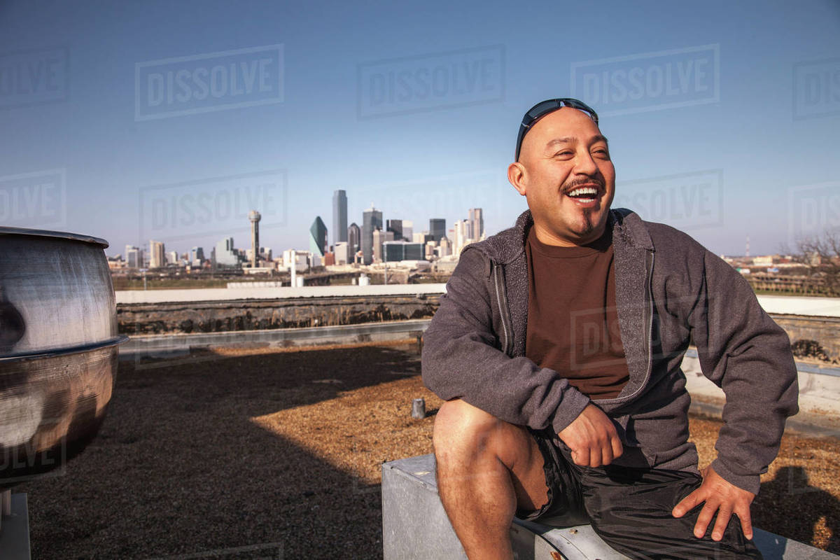 Laughing man sitting on rooftop Royalty-free stock photo