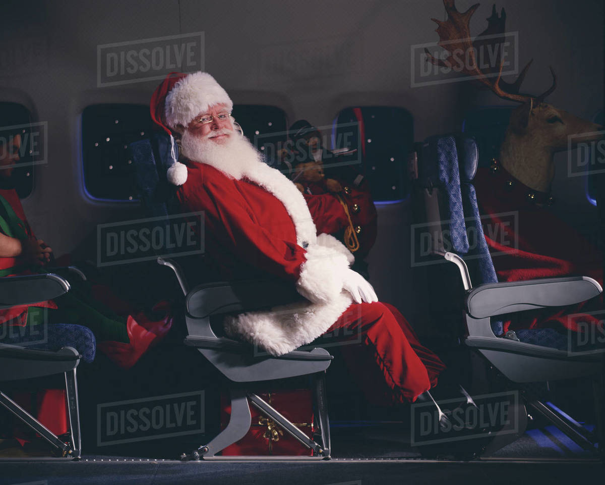Santa Claus, elves, reindeer and presents on an airplane Royalty-free stock photo