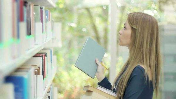 Female college student taking book from shelf in library and looking at camera Royalty-free stock video