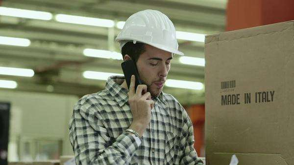 Portrait of young man employed in logistics facility talking on mobile phone, people working in warehouse, workers in industry. Royalty-free stock video