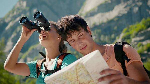 Man and woman during leisure activities on holidays, young people hiking and trekking on mountains, talking, and looking at map with binoculars Royalty-free stock video