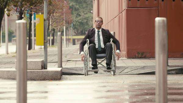 Businessman on wheelchair crossing a city street with car and traffic Royalty-free stock video