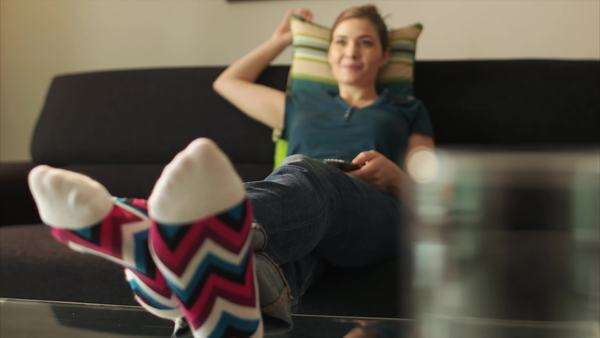 Young woman laying on sofa with colorful socks. She puts her feet on table and sits back. The girl watches TV and holds remote control Royalty-free stock video
