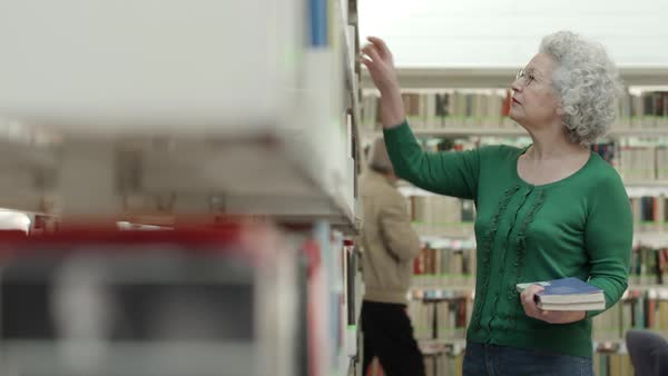 Portrait of old retired woman choosing book in library and taking it from shelf. Dolly shot Royalty-free stock video