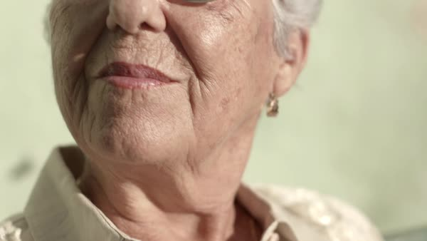 Portrait of senior caucasian woman with glasses looking at camera and smiling. Close-up of face Royalty-free stock video