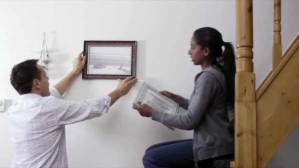 Interracial couple hanging pictures to the wall at home, home improvement and decoration, diy Royalty-free stock video