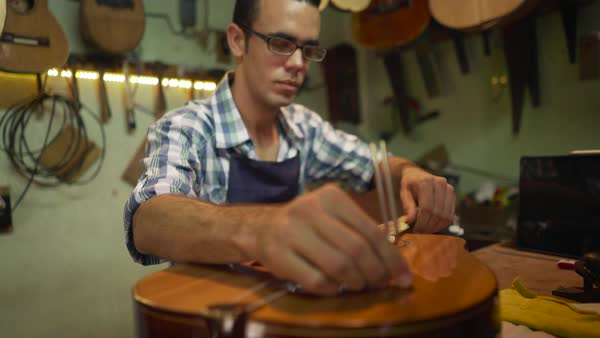 Lute maker shop and classical music instruments: young adult artisan fixing old classic guitar, tuning the instrument with a metallic diapason Royalty-free stock video